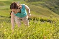 Female golfer searching in grass for golf ball