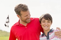 Father with an encouraging arm around preteen son on golf course