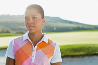 Pretty, African American female golfer gazing off on golf course
