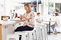 Young woman texting at bar counter (thumbnail)