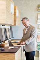 Man looking at samples of wood