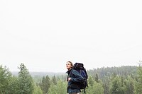 Mid_adult man backpacking in the woods