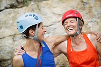 Female rock climbers hugging and laughing