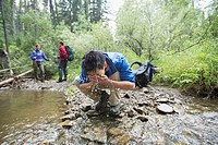 Male hiker washing his face in a stream.