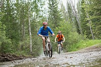 Two male mountain bikers riding through stream