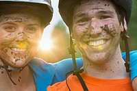 Portrait of mountain biking couple with mud on their faces.