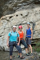 Portrait of three rock climbers standing in front of rock face