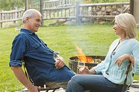 Middle_aged couple enjoying a glass of wine by an outdoor fire