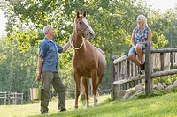Couple looking at horse on their rural property