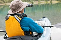 View from behind of woman with binoculars in kayak.
