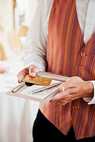 Waiter holding tray with receipt and credit card