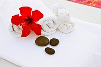 Still life with red flower, pebbles and towels