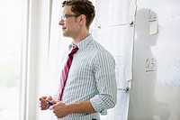 Mid_adult businessman standing in front of whiteboard