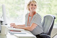 Middle_aged businesswoman sitting at desktop computer