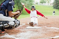 Young male baseball player sliding into home