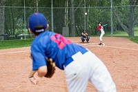 Pitcher on boys baseball team throwing ball to batter