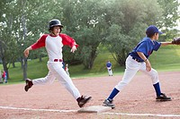 Young baseball player running for first base.