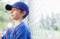 Young male baseball player watching game from sidelines (thumbnail)
