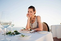 Woman sitting at dinner table in outdoor restaurant (thumbnail)
