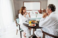 Couple having breakfast in hotel room