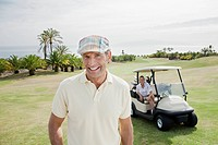 Portrait of smiling man on golf course with woman sitting in golf cart in background
