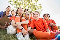 Girls soccer team smiling with oranges in their mouths (thumbnail)