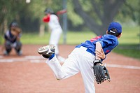 View from behind of young male pitcher throwing baseball