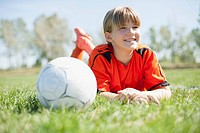 Girl soccer player lying on grass with soccerball