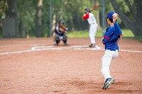 Young baseball pitcher winding up to throw baseball