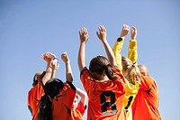 Soccer girls with arms raised in a cheer