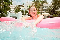 Girl 6_7 on inflatable toy in swimming pool