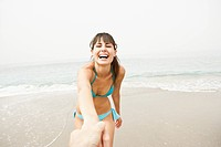 Laughing young woman on beach (thumbnail)