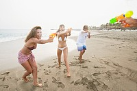 Happy friends playing with water guns