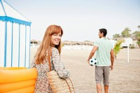 Young couple on beach, woman looking at camera