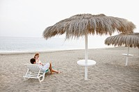 Couple resting on beach lounger