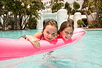 Two girls 6_9 on inflatable toy in swimming pool