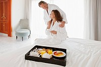 Couple in bedroom with breakfast on bed