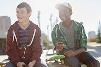 Teenage boys with smart phones at skate-park (thumbnail)