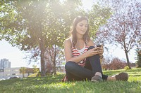 Young adult woman texting on smart phone in park