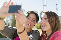 Teenage girls taking self portrait with smart phone