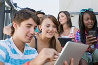 Teenagers sharing wireless technology outdoors