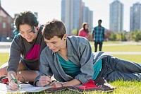 Teenage couple doing homework together in park