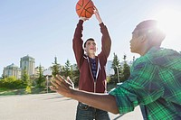 Teenage boys playing basketball at outdoor park