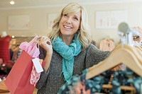 Pretty, middle-aged woman shopping in clothing store (thumbnail)
