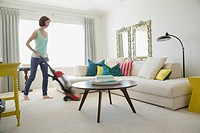 Mid_adult woman vacuuming her contemporary living room