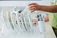 Woman putting clean dishes into dish rack to dry