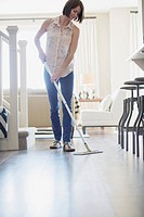 Mid_adult woman dusting modern wood floor