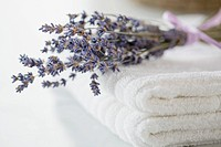 Folded white towels with sprig of lavender