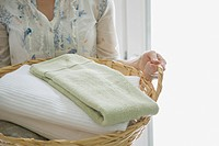 Mid_adult woman carrying wicker basket of folded towels
