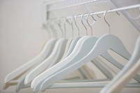 Close_up of white clothes hangers in closet